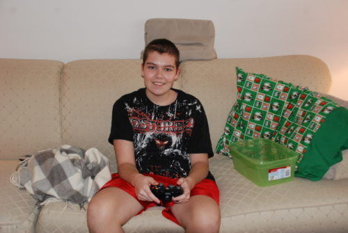 Andrew playing X-Box on a tan couch. He's wearing red shorts and a black t-shirt with a masked super hero on it.