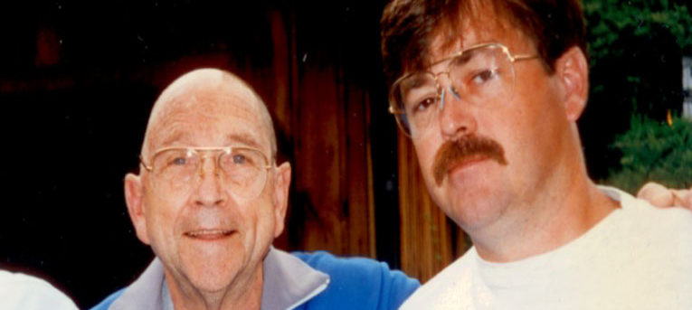 Jerry and his dad. Jerry's dad is bald, wearing glasses, a gray tshirt and a blue jacket with gray color. Jerry is wearing glasses and white t-shirt and has a mustache