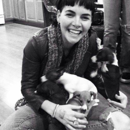 Jessie sitting with puppies. It's a black and white photo. She's wearing a leather jacket and blue jeans. She has a scarf on and a ring in her nose.