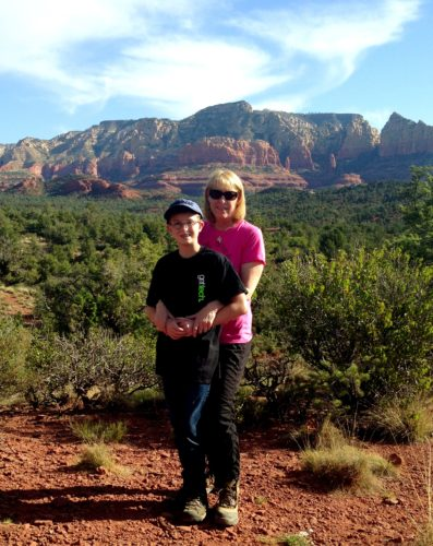 Ann and one of her sons standing against the backdrop of the AZ mountains. Ann is wearing a short sleeve pink shirt and black pants. Her son is wearing glasses, a baseball cap, jeans and a short sleeve black t-shirt