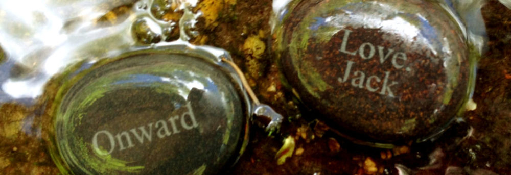 """Jack's stones. The front (shown on the left) says """"Onward"""". The bottom (shown on the right) says """"Love Jack)."""