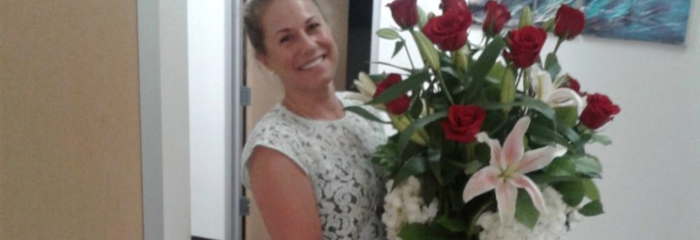 Steph in a hallway carrying a huge bouquet of red roses and greenery in a glass vase. Her hair is up, and she's wearing a no sleeve white print shirt and blue jeans