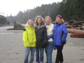 Reba's four closest friends on the beach. The friend on the left is wearing a yellow jacket and jeans. She has blond hair. The next friend has light hair and is wearing a dark jacket and blue jeans. The third friend has a light yellow long sleeve shirt on with a jacket tied around his waist and blue jeans. The friend on the other end is wearing a beanie, a royal blue jacket and black pants