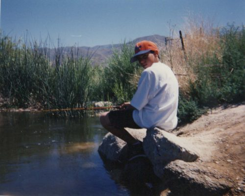 Kyle age 12 sitting on a rock fishing in the Owen's River. He's wearing a red baseball cap, white t-shirt and dark shorts