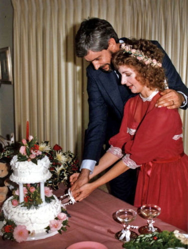 Jan and Cliff on their wedding day cutting a white two-tiered wedding cake with flowers on it. Cliff is wearing a dark suit and has his left arm around Jan. His right hand is on Jan's as they cut the cake. Jan is wearing a 3/4 sleeve length red dress and a garland of pink roses in her hair
