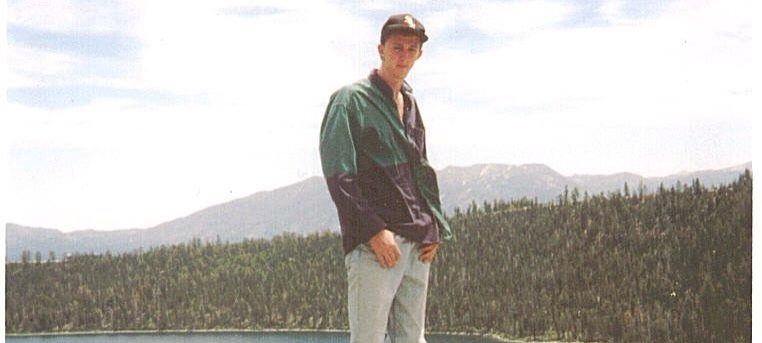 Seth standing on a rock in front of a large lake with pine trees and another mountain in the background. He's wearing light blue jeans, black shoes, a green jacket and a baseball cap