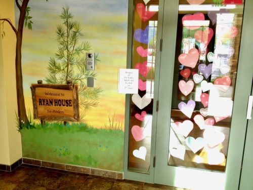 """Ryan House. A photo of the wall outside the entrance and the front door. The wall has a painting of grass, a pine tree and a wood sign that says """"welcome to Ryan House"""". The glass front door and the window to the left of the door are covered with different color hearts"""