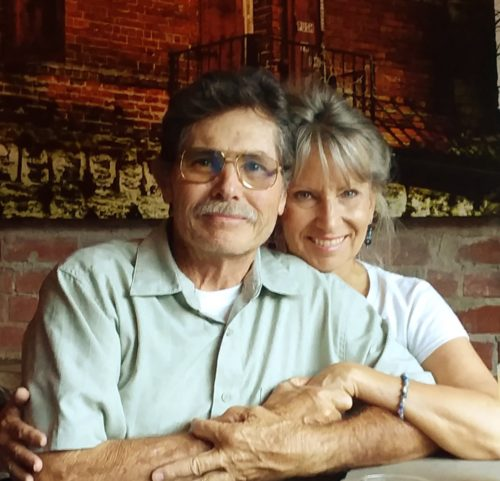 Wayne and Jean 3 years after Kyle's death. Wayne is wearing a light green short sleeve button shirt with a color and a white tshirt beneath it. He has a mustache and is wearing glasses. He has dark hair. Jean has blond hair and is sitting behind and to the left of Wayne. Her right arm is around his shoulders and her left arm is over Wayne's left arm, and she is holding his hand. She's wearing a short sleeve white shirt.