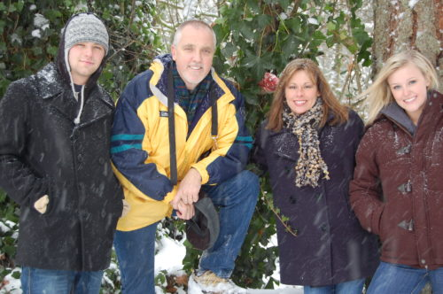 Conner, Kevin, Kevin's wife and daughter in the snow. Conner is wearing a dark ski jacket and gray skull cap. Kevin is wearing a blue and yellow ski parka and jeans. Kevin's wife is wearing a scarf and navy blue long parka. Kevin's daughter is wearing blue jeans and a burgundy coat.