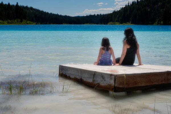 Mother and daughter sitting on a wooden dock. The water goes from light blue to dark blue as it gets closer to the distant mountains covered with trees. The daughter is wearing a blue print swimsuit. The mother is wearing a sleeveless black dress and has long brown hair