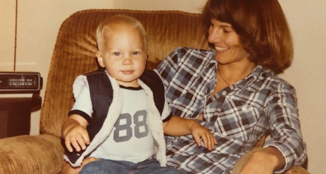 Heidi is sitting on a brown chair. Scott is about two. He's sitting on her lap wearing a dark vest with white trim, a white t-shirt with the number 88 on it and jean pants. His hair is white blond. Heidi's hair is dark brown. She's wearing a black and white checked shirt and light blue jeans. She's looking at him, and he's looking at the camera
