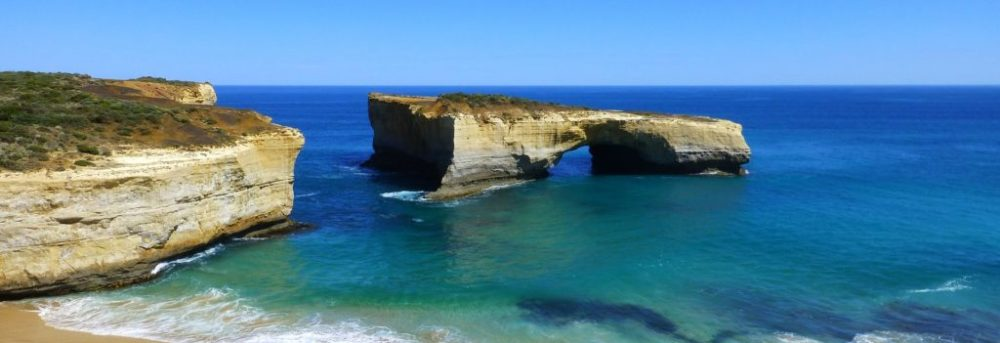 London Bow, Australia under a clear blue sky. The sand is visible in the front of the picture and the green blue water in front of it with deeper blue water behind it