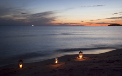Three lit lamps in a row on the sand in front of the ocean at sunset