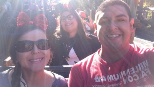 Rudy and Aly. Aly is on the left wearing sunglasses, a braid over her right shoulder and a sparkly red bow in her hair. Aly is behind and in between Aly and Rudy wearing black Mickey Mouse ears, glasses and a black and white t-shirt. Rudy is on the right wearing a red t-shirt with white writing.