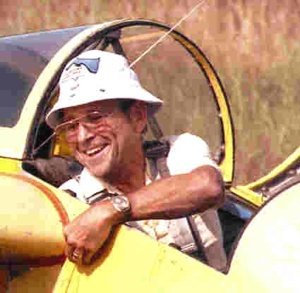 Jerry's dad in the cockpit of a yellow plane. He's wearing a wristwatch and wedding band on his left hand. He's wearing a white hat, white shirt and glasses