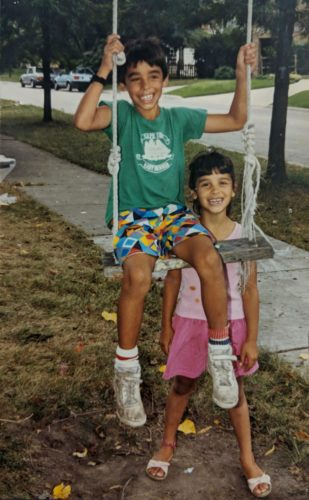 Carlos is on a swing. He's wearing bright print board shorts, white tennis shoes and a green tshirt. MarKee is standing behind the swing and is wearing a light pink short sleeve shirt and darker pink shorts