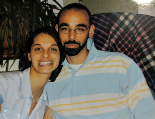 Markee is on the left wearing a light blue blouse. Carlos has a dark beard and mustache and is wearing glasses and a colored blue and white broad stripe shirt with thin yellow stripes in the white stripes