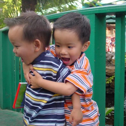 Matthew hugging Ryan. Matthew is wearing an orange, blue and white striped shirt. Ryan is wearing a blue, light blue, white and gold striped shirt. They're facing the left with Matthew behind Ryan and standing in front of a green fence