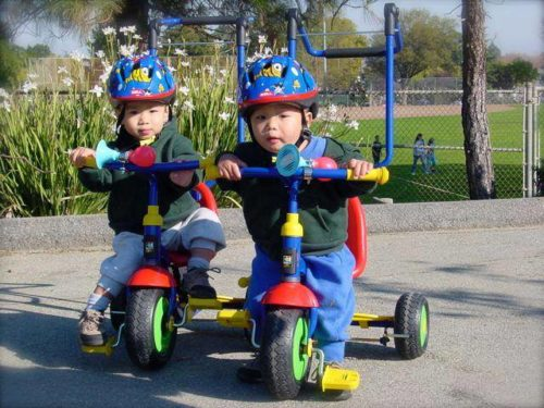 Matthew and Ryan riding red, green, yellow and blue tricycles, wearing blue helmets with red trim. They're both wearing olive green jackets and blue pants