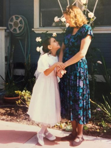 Jess at age 10 or younger wearing a short sleeve white dress looking up at her mom. Bernie is holding Jess' hands and wearing a cap sleeve blue, purple and black dress.