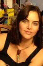 Jess wearing a black tank top and carnelian colored stone on a short necklace looking at the camera. She has brown hair parted on the left side