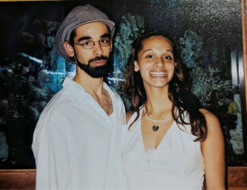 Carlos is on the left. He has a beard and mustache and is wearing glasses, a long sleeve white shirt and a gray hat. Mar'Kee is wearing a white sleeveless shirt. Her hair is long, and she is wearing a pearl necklace with a metal heart in the middle