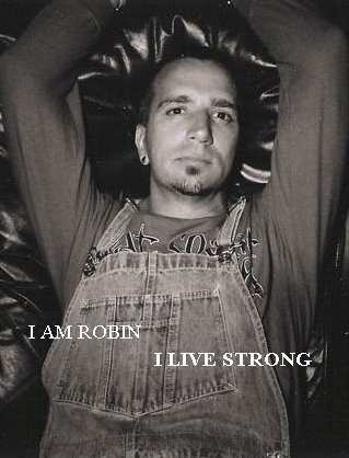 Black and white photo of Robin. He's wearing overalls and a long sleeve t-shirt. He has an earring in his right ear, a bit of hair under his lower lip and a goatee. His arms are raised above his head and crossed at the elbow
