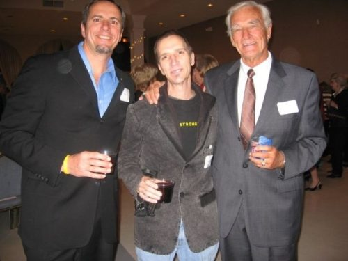 Chris on the left wearing a black suit and light blue button down shirt. He's holding a drink in his right hand and has a goatee. Robin is in teh middle wearing a black LIVESTRONG t-shirt under a dark gray suit jacket and blue jeans. The word LIVESTRONG is written in yellow across his chest. Their stepfather is on the right. He's also holding a drink and has white hair. His right arm is around Robin, and he's wearing a gray suit and reddish colored tie