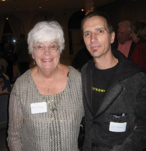 Chris and Robin's mom and Robin. Their mom has white hair and glasses and she's wearing a light gray top and a name tag. Robin is wearing a black suit jacket and a black t-shirt with the word LIVESTRONG written in yellow across it
