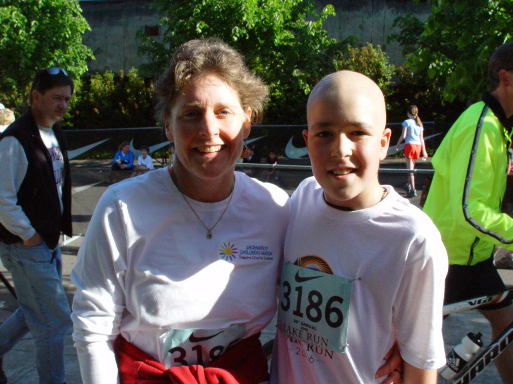 Margo and Jimmy after a race. They're both wearing white t-shirts. Jimmy is bald and Margo's hair is pulled back in a pony tail