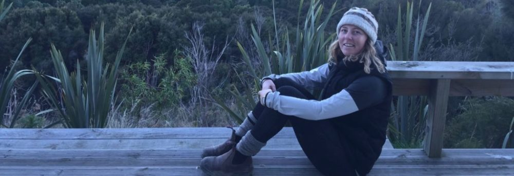 Tessa sitting on a wooden bench outside in front of green grasses and wild flowers. She is sitting with her knees bent sideways to the camera. Her arms are around her knees. She has a white and brown knit cap on, a long sleeve gray shirt with a short sleeve black t-shirt over it, black pants, gray socks and hiking boots