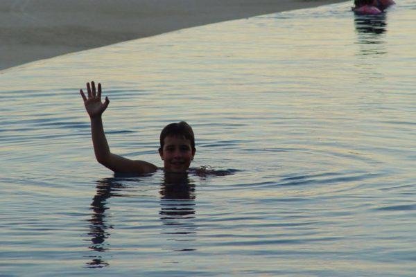 Jimmy in an infinity pool in Mexico. Only his head and his right arm is above the water. He's waving