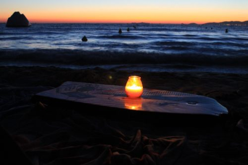 A candle in a glass on top of a picnic table with the dark blue ocean and orange of the sunset behind it