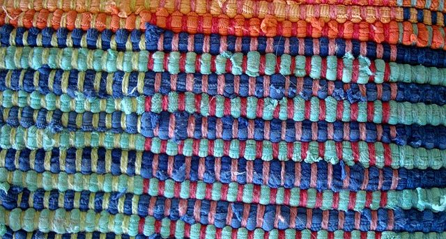 Woven rug with squares of varying colors.