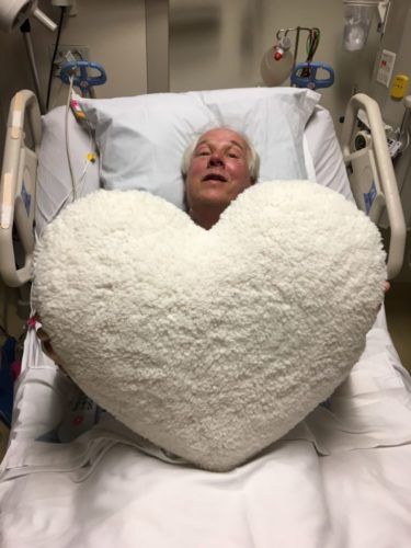 Dick in a hospital bed with white sheets on it. He's holding a huge white heart pillow that covers all but his head.