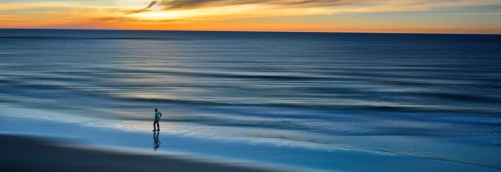 The ocean at sunset. There's the silhouette of a man walking on the left. The water is varying shades of blue. The sky is cloudy with some orange.