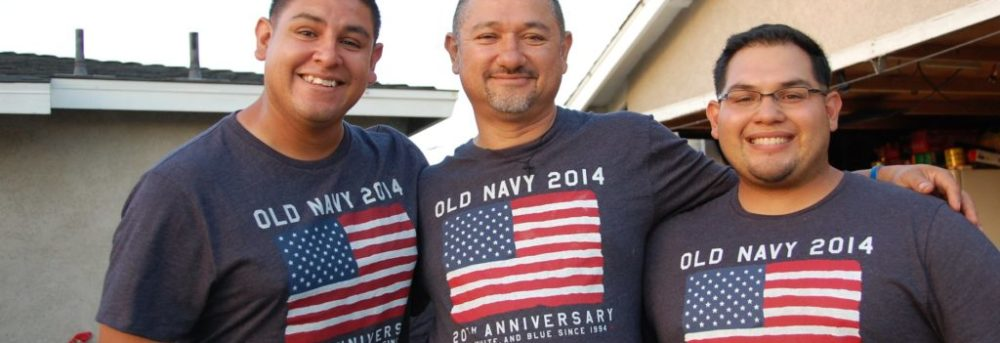 "rudy dad andy. They're all wearing navy t-shirts with the American flag. Above the flag it says ""Old Navy 2014"""