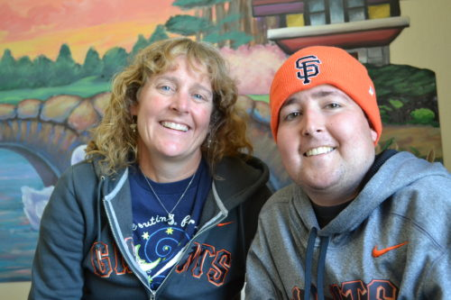 Margo & Jimmy at Family House. Margo is wearing a blue t-shirt with an SF Giants gray sweatshirt with orange writing. Jimmy is wearing a gray pullover sweatshirt with SF Giants written in orange and black across it. He's wearing an orange Giants skullcap with SF in black in the front