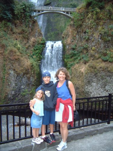 Molly, Jimmy and Margo in front of a wrought iron fence in front of Willamette Falls. Molly is on the left wearing a light blue tank top, blue shorts and a blue baseball cap worn backwards. Jimmy is wearing blue basketball shorts, a navy sweatshirt and a navy baseball cap worn backwards. Margo is wearing white shorts, a royal blue tank top and a melon sweatshirt tied around her waist.