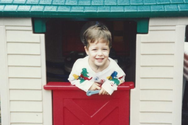 Jimmy, wearing a white long sleeve t-shirt, with different primary color dinosaurs on it. The playhouse has a green roof, red door and tan walls.