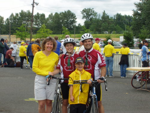 Margo, Jimmy, Molly and Dan at the 2006 Portland LIVESTRONG Challenge. Jimmy and Dan are wearing white bike helmets, holding their bikes and wearing Stanford bike jerseys. Margo is wearing a long sleeve yellow shirt and khaki shorts. Molly is wearing a LIVESTRONG hat, black with yellow writing, a LIVESTRONG bike jersey, black shorts and a yellow LIVESTRONG vest with a black stripe across her chest.