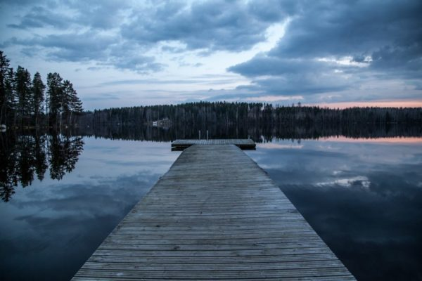 Wooden dock stretching into the distance. Beyond it is a row of trees. Water is on both sides. The sky is cloudy. and dark. The sun has set in the right of the picture leaving a faint bit of orange above the trees and reflected on the water.