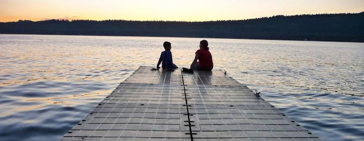 Eve and a younger sibling sitting at the end of a dock as the sun begins to set. The sky is light yellow with blue water between it and the kids