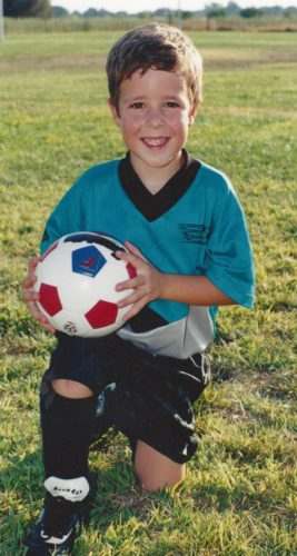 Jimmy in a teal soccer jersey withe black trim. He's kneeling on his left knee and his right knee out in front at a 90 degree angle with his black cleat on the grass. he's wearing black soccer socks and black shorts and is holding a white soccer ball with two red patches and one blue patch.