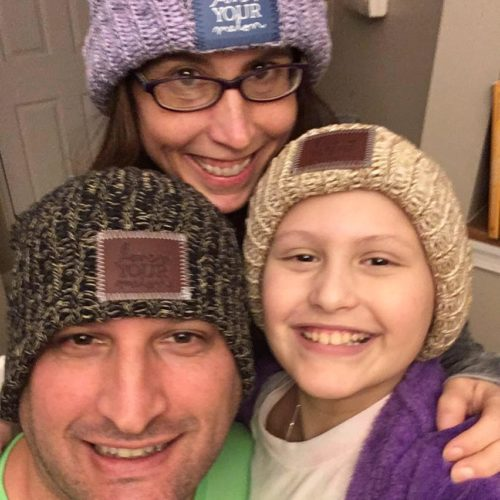 Erica, her husband and Ariella all wearing Love Your Melon hats. Dad is wearing a black gray & tan knit hat. Erica is wearing black rimmed glasses and a light purple hat. Ariella is wearing a light tan hat, white tshirt and purple jacket