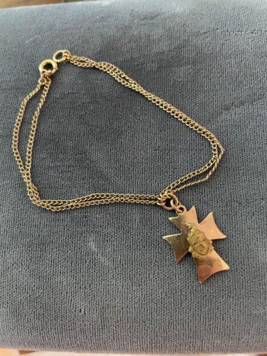 Gold cross on double gold chain resting on gray velvet.
