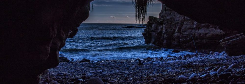 Dark cave at nightfall with a rocky beach in the foreground and the ocean and a dark blue sky in the background