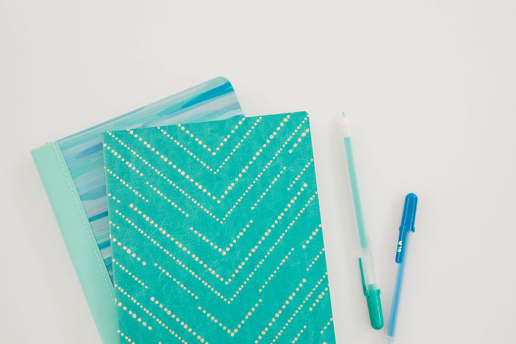 """green and blue gel pens on the right forming a 30 degree angle with the green on the top. On the left, two notebooks. The top one has green stripes in the shape of """"v""""s."""