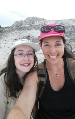 Clara and Tamara. Clara is on the left wearing glasses, a light tan t-shirt and a white baseball cap and glasses. Tamara is wearing a black tank top and a fluorescent pink baseball cap with sunglasses perched on the cap
