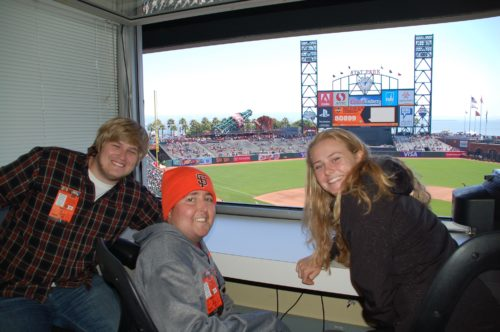 Griffin, Jimmy & Delaney at the Giants' game. Griffin is wearing a plaid shirt with a white undershirt and is leaning on his left elbow. Jimmy is wearing an orange Giants' beanie and a gray Giants' sweatshirt with orange writing across the chest. Delaney is wearing a black hoodie. She has long blond hair.